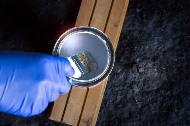 Penseel in zijn hand wordt gedoopt in een potje verf op een donkere achtergrond met een kopie van de ruimte.