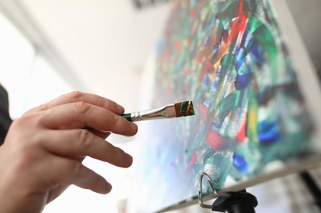 Penseel om in de hand te schilderen en kunstenaar maakt schetsen. hedendaags kunstconcept