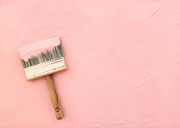 Penseel op roze achtergrond met pas geverfde textuur