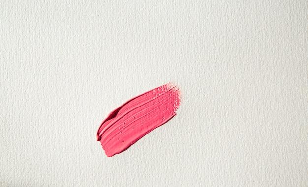 Penseelstreek van roze verf met glitter op wit aquarelpapier roze uitstrijkje
