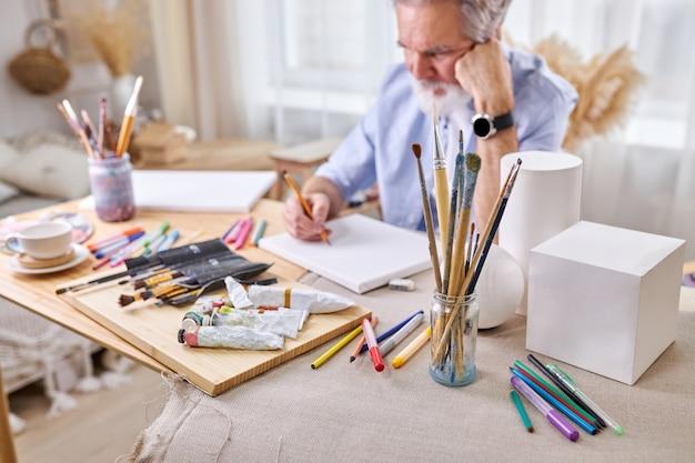 Penselen in glazen blikken en gouache, verf, potloden op tafel en bedachtzame schilder. kunst concept