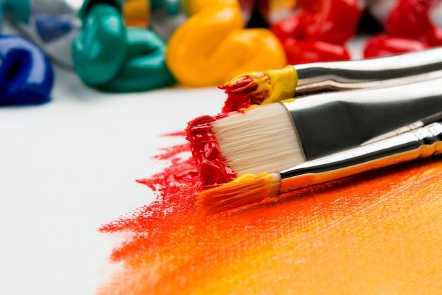 Penselen om te schilderen in veelkleurige verf op een achtergrond van olieverf op een licht doek