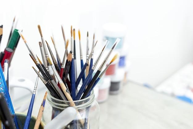 Penselen van de kunstenaar in een pot in een schildersatelier