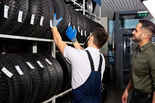 Pensioen man aanraken en kiezen voor het kopen van een band, het meten van het rubberen autowiel, het uit de plank met het assortiment halen