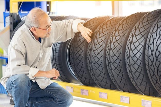 Pensioen man aanraken en kiezen voor het kopen van een band in een supermarkt-winkelcentrum. rubberen autowiel meten.