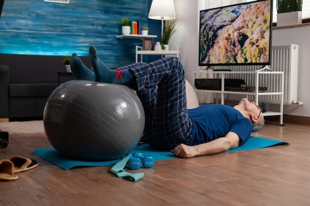 Pensioen senior man doet wellness opwarmende benen met behulp van zwitserse bal zittend op yogamat in het leven ...