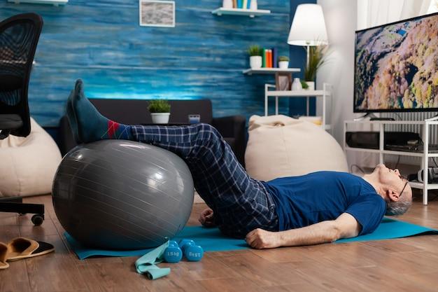 Pensioen senior man doet wellness opwarmende benen met zwitserse bal zittend op yogamat in woonkamer in