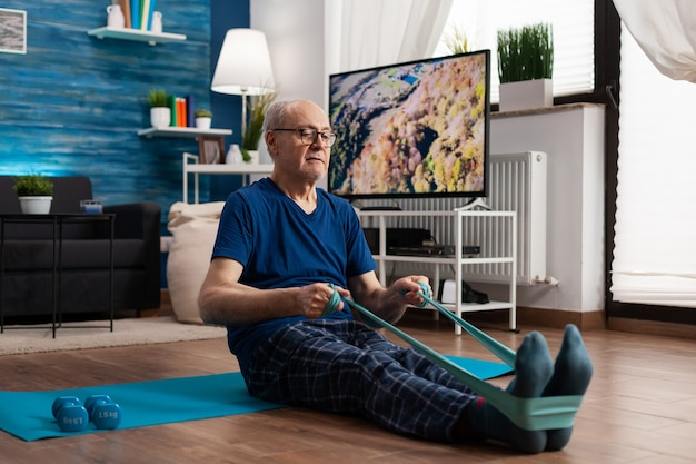 Pensioen senior man zit op yoga mat benen spieren uitrekken