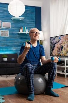 Pensioen senior man zittend op de zwitserse bal uitoefening van de armen spieren doen fitness oefeningen met behulp van training halters. gerichte gepensioneerde die lichaamskrachtweerstand traint in de woonkamer