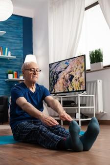 Pensioen senior man zittend op yoga mat benen spieren strekken tijdens lichaamstraining werken aan flexibiliteit
