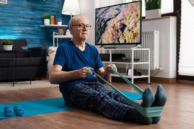 Pensioen senior man zittend op yoga mat benen spieren uitrekken met behulp van weerstand elastische band opleiding lichaamsflexibiliteit. gepensioneerde in sportkleding afvallen tijdens spiertraining in woonkamer