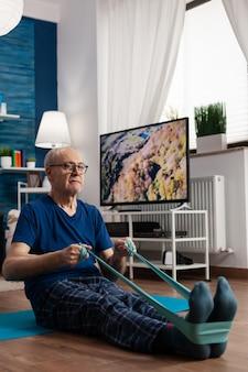 Pensioen senior man zittend op yoga mat benen spieren uitrekken met behulp van weerstand elastische band trai...