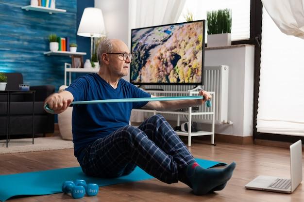 Pensioen senior man zittend op yoga mat met been in gekruiste positie armen spieren uitrekken met behulp van elastische elastische band tijdens sport routine in woonkamer