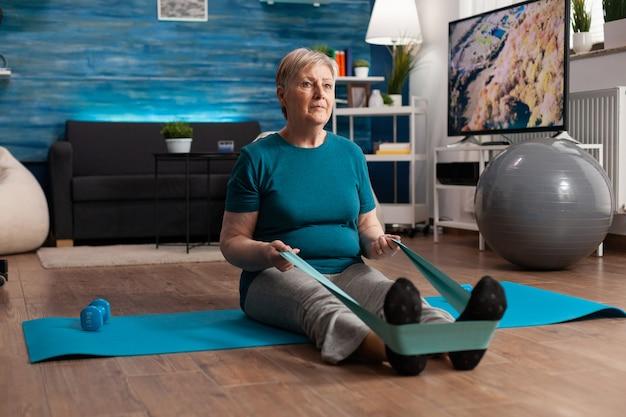 Pensioen senior vrouw zittend op yoga mat stretching benen spieren met behulp van elastische elastische band training lichaamsweerstand