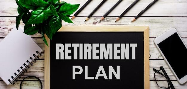 Pensioenplan is in het wit geschreven op een zwart bord naast een telefoon, notitieblok, bril, potloden en een groene plant