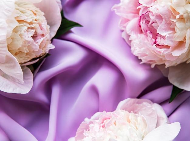 Peony bloemen op een violette zijden tafel