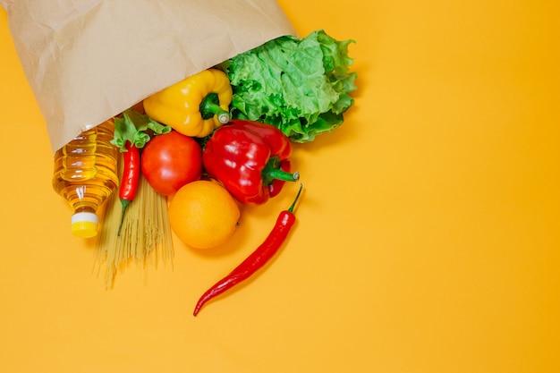 Peper, chili, zonnebloemolie, tomaat, sinaasappel, pasta, sla in papieren knutselpakket, papieren zak met een set van verschillende groenten en fruit op een gele ruimte