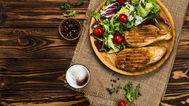 Peper en bier in de buurt van salade en kip