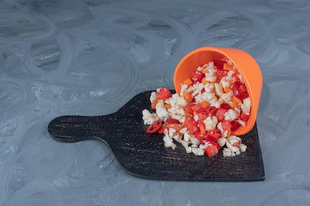 Peper en bloemkoolsalade gieten uit een kom op een zwart bord op marmeren tafel.