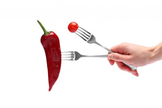 Peper en tomaat op vorken op witte achtergrond