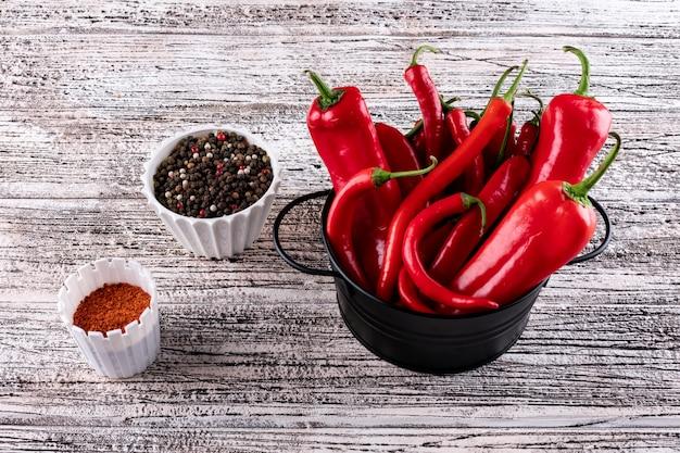 Peper van de zijaanzicht de rode spaanse peper in zwarte pan met kruiden