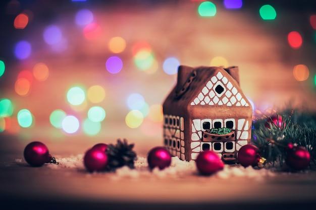 Peperkoek huis en kerstballen op feestelijke achtergrond. de foto heeft een lege ruimte voor uw tekst