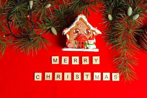 Peperkoek huis in takken van de kerstboom op rode vilt achtergrond