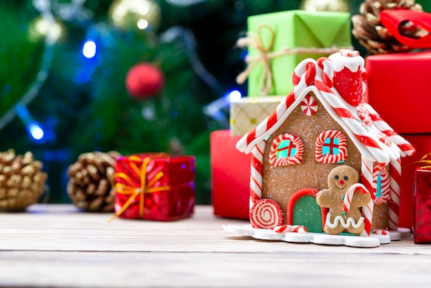 Peperkoek huis op een houten tafel, samen met kerstcadeaus op de van een kerstboom.