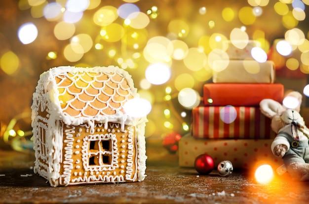 Peperkoek huis vele geschenken in kraft inpakpapier en lichten bokeh op donkere achtergrond,