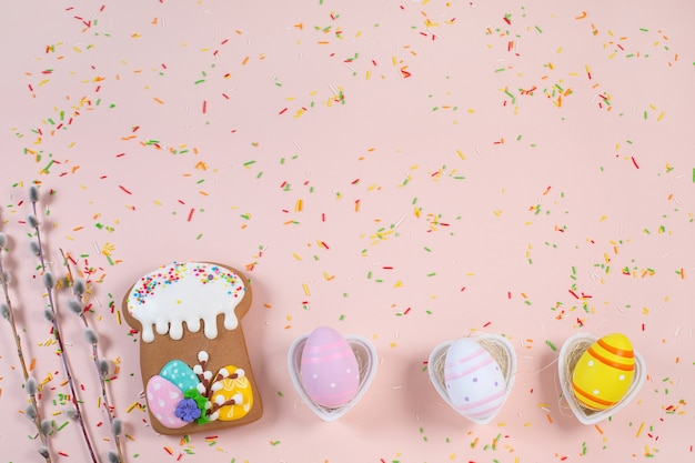 Peperkoek in de vorm van een cake van pasen en kleurrijke eieren op een licht bureau