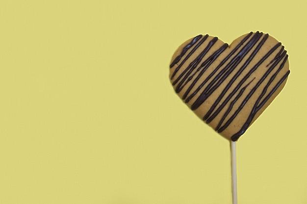 Peperkoek in de vorm van een hart met een chocolade op een gele achtergrond.
