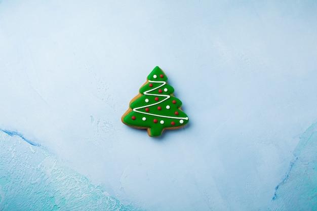 Peperkoek in de vorm van kerstbomen op blauw.
