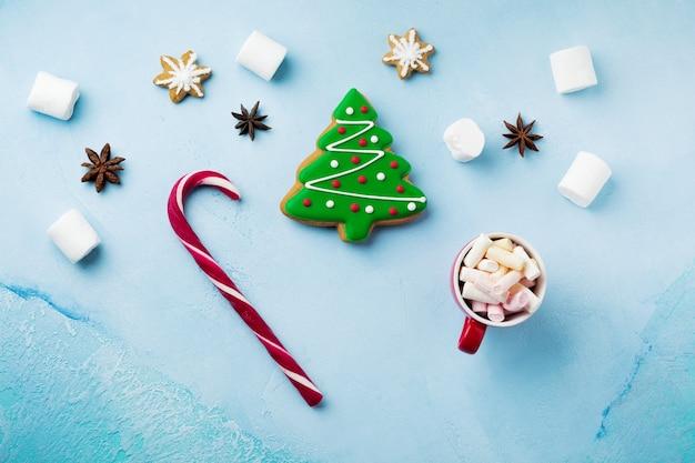 Peperkoek in de vorm van kerstbomen op een blauw, een kop warme chocolademelk en snoep in kinderhanden.