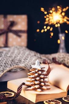 Peperkoek kerstboomkoekjes, geopend boek met de inscriptie op de pagina januari. sparklers en cadeau in een doos.