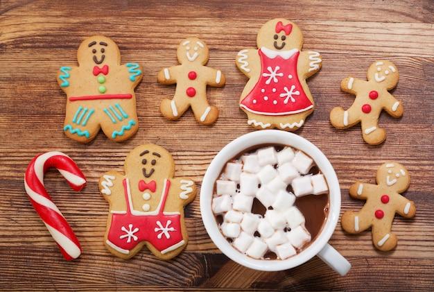 Peperkoek kerstkoekjes en kop warme chocolademelk op houten tafel, bovenaanzicht