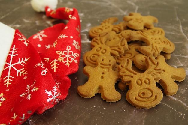 Peperkoek kerstkoekjes en santa claus rode hoed geïsoleerd op een witte achtergrond. detailopname