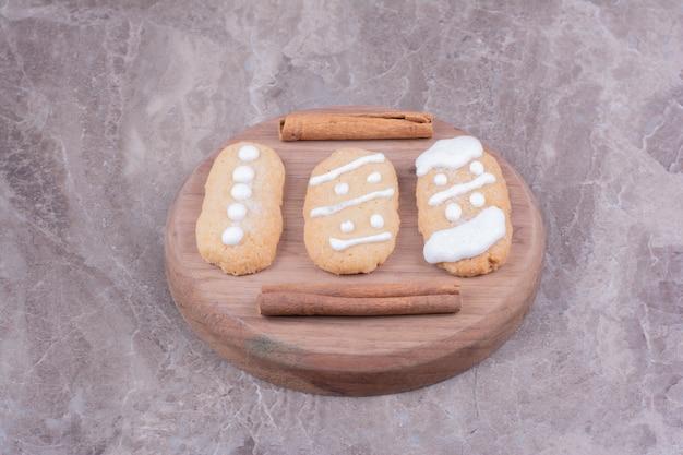 Peperkoek kerstkoekjes met kaneelstokjes op ronde houten bord.