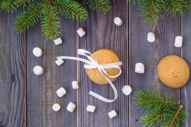 Peperkoek kerstkoekjes met versieringen en marshmallows op achtergrond met kerstboom.