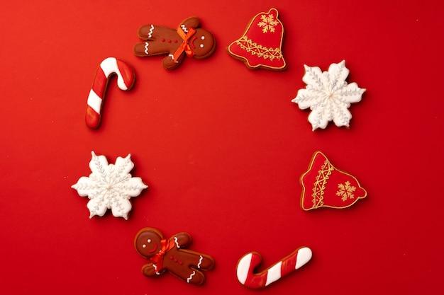 Peperkoek kerstkoekjes op rode achtergrond bovenaanzicht, kopie ruimte