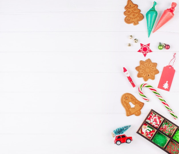 Peperkoek kerstkoekjes, suikerglazuur zakken, beregening en decor op witte houten achtergrond. bovenaanzicht, plat gelegd.