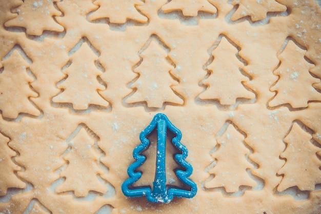 Peperkoekdeeg voor koekjes in vorm van kerstbomen met plastic snijder.