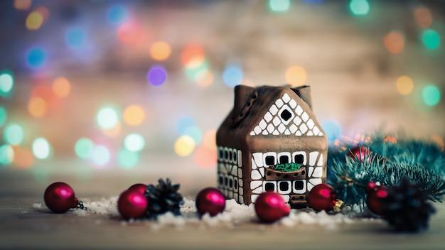 Peperkoekhuis en kerstballen op feestelijke achtergrond. de foto heeft een lege ruimte voor uw tekst