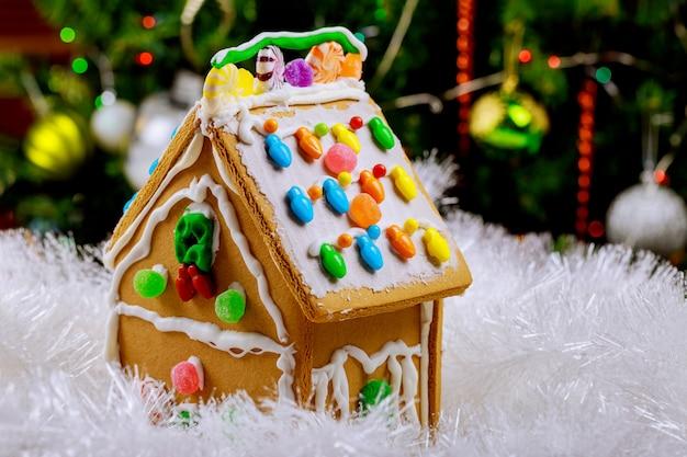 Peperkoekhuis in sneeuw op de verfraaide oppervlakte van de kerstmisboom