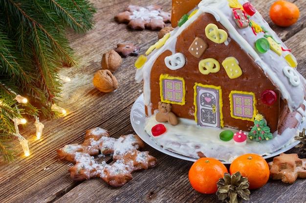 Peperkoekhuisje met mandarijnen en kerstverlichting