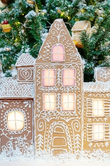 Peperkoekhuisje onder de kerstboom. feestelijke achtergrond.