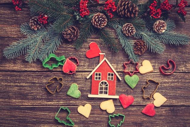 Peperkoekkoekje en huisstuk speelgoed dichtbij dennentak op een houten lijst.