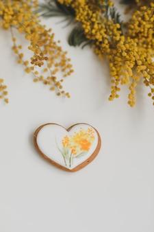 Peperkoekkoekje in een vorm van een hart en mimosa bloemen op witte achtergrond. bovenaanzicht kopie ruimte