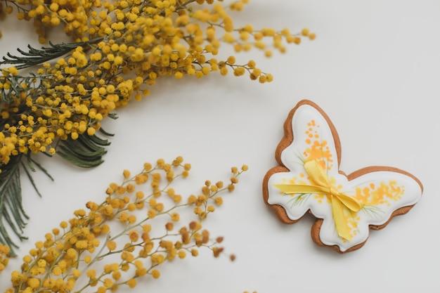 Peperkoekkoekje in een vorm van een vlinder en mimosa bloemen op witte achtergrond. lente, vrolijk pasen-concept. bovenaanzicht kopie ruimte