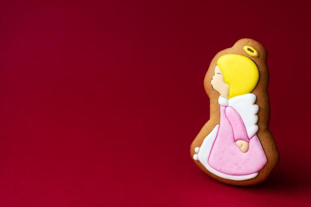 Peperkoekkoekje van schattige engeltjes op rood. traditioneel kersteten. kerstmis en nieuwjaar vakantie.