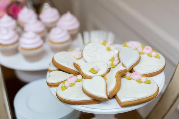 Peperkoekkoekjes en koekjes op de feesttafel met snoep. stijlvol gebak als decoratie voor de feestdagen. zoete reep